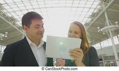 Young happy businesspeople using pad in office building -...