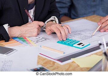 Estimating project cost - Close-up of interior designers...
