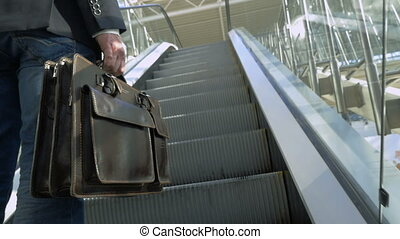 Businessman with leather briefcase riding on escalator -...