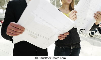 Man and woman looking at construction plans - Slow motion...