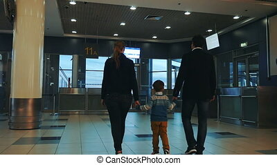 Family of three walking in airport terminal - Slow motion...