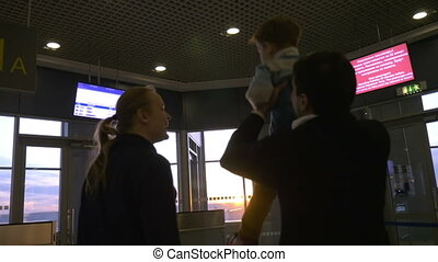 Family at airport terminal looking outside at sunset