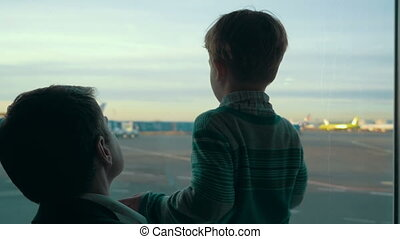 Son and dad looking at airport area through the window