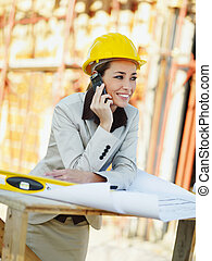 female architect talking on mobile phone in construction...