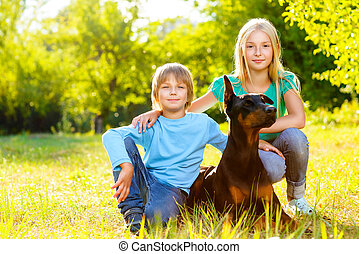 Adorable boy and girl in summer park with their dog.