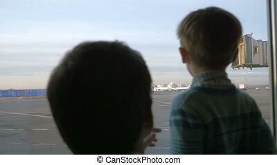 Father and son looking out the window at airport