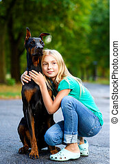 blonde girl hugs her beloved dog or doberman in summer park.