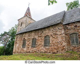 Old, ancient abandoned church in forest at summer time