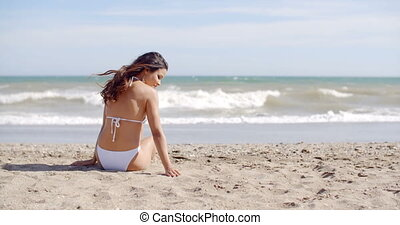 Pretty young woman relaxing on a beach in her bikini facing...