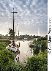 Boats moored on riverbank at sunrise in countryside...