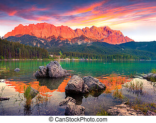 Colorful summer sunset on the Eibsee lake in German Alps...