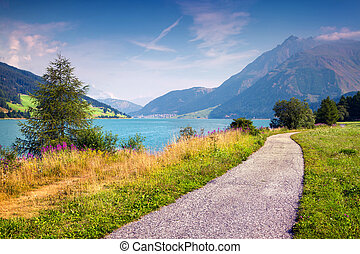 Bicycle path around Resia lake in the Italian Alps. Colorful...