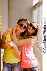 Two happy pretty teenage girls in sunglasses hugging -...