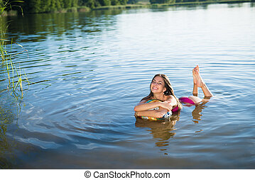 Young happy smiling girl hugging big ball splashing in lake...