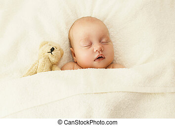Portrait of cute baby sleeping together with teddy bear toy...