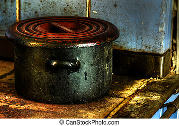 Old dirty enamel pot on stove.