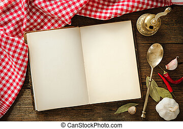Open cookbook with kitchenware on checkered tablecloth