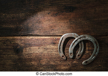 Two old rusty horseshoes on vintage wooden board