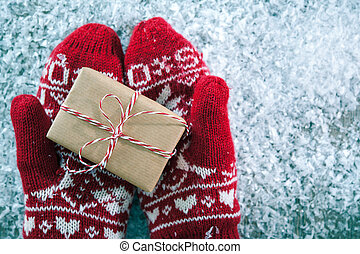 Christmas gift - Female hands in winter gloves with...