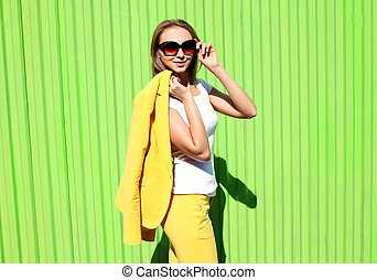 Fashion elegant young woman in yellow suit clothes and...