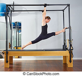 Pilates woman in cadillac legs split reformer exercise at...