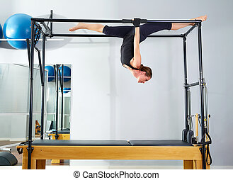 Pilates woman in cadillac walk over reformer upside down...
