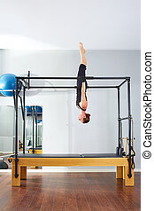 Pilates woman in cadillac acrobatic upside down balance...