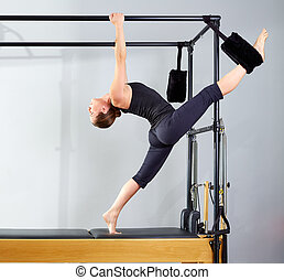 Pilates woman in cadillac split legs stretch exercise at gym