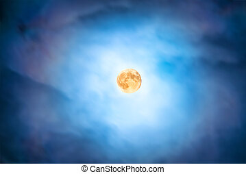 Night view at the full moon through moving blue clouds...