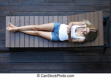 woman laying on wooden sunbed - young woman laying on wooden...