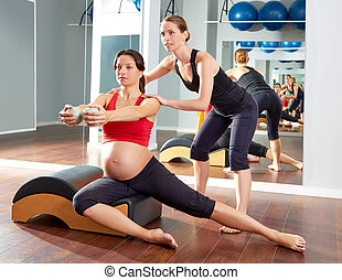 pregnant woman pilates side stretchs exercise workout at gym...