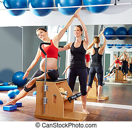pregnant woman pilates side stretch exercise on wunda chair...