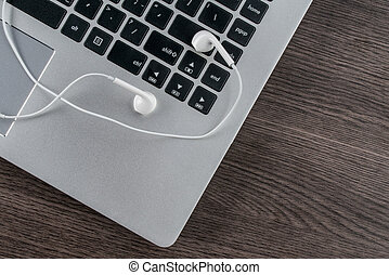 earphone with laptop on the wood desk