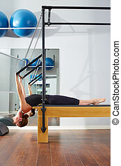 Pilates woman in reformer exercise at gym indoor