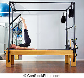 Pilates woman in reformer tower exercise at gym