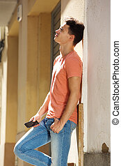 Handsome young man standing outside with cell phone