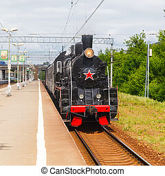 old black steam locomotive in Russia at the summer on a...