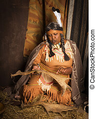 Native American storyteller - Weathered mature tribal female...