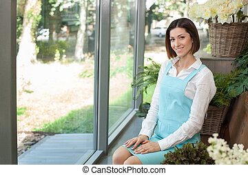 Cheerful young florist is resting in her store - Attractive...