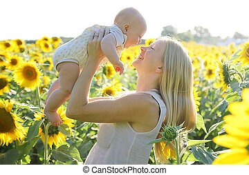 Happy Mother and Baby Daughter in Sunflower Field - A happy...
