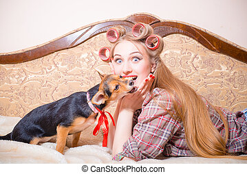 Excited young beautiful girl with curlers and dog - Closeup...