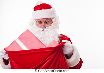 Cheerful Santa Claus is carrying a bag of presents -...