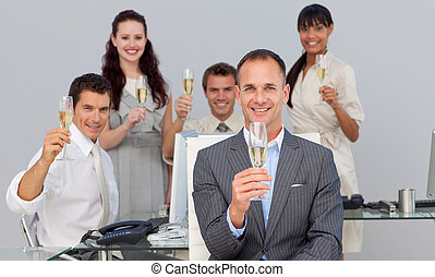 Successful business co-workers toasting with Champagne in...