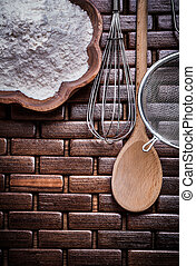 Set of wooden spoon bowl flower sieve and egg-whisk