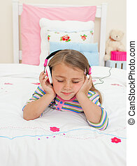 Beautiful Little gril listening to music lying on her bed -...