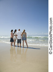 family holding hands looking out to surf