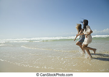 two sisters running on beach holding hands