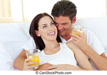 Young couple drinking orange juice lying on their bed at...