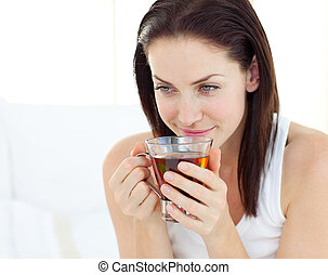 Smiling woman drinking a cup of tea