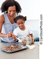 Smiling mother helping her daughter cooking biscuits in the...